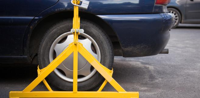 Rozporządzenie ministra spraw wewnętrznych i administracji określa, że blokowanie kół pojazdu następuje przez zastosowanie urządzenia technicznego do blokady kół, zwanego blokadą
