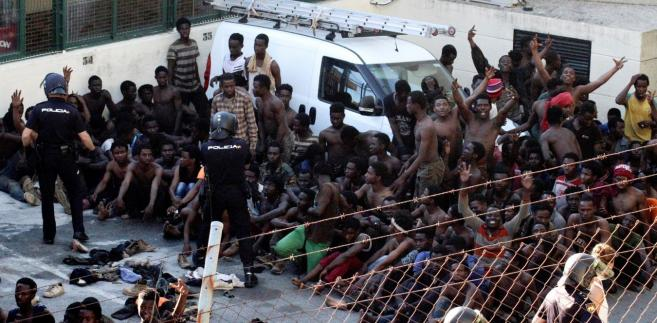 Migranci sztormujący ogrodzenie w hiszpańskiej Ceucie